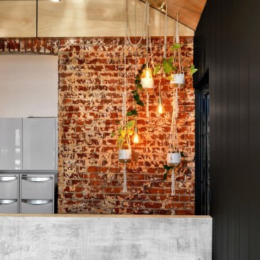 Exposed brick wall and black wood panelling in the Think Architects studio