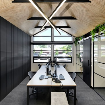 Interior of the Think Architects studio with racked ceiling, exposed beams and barn sliders
